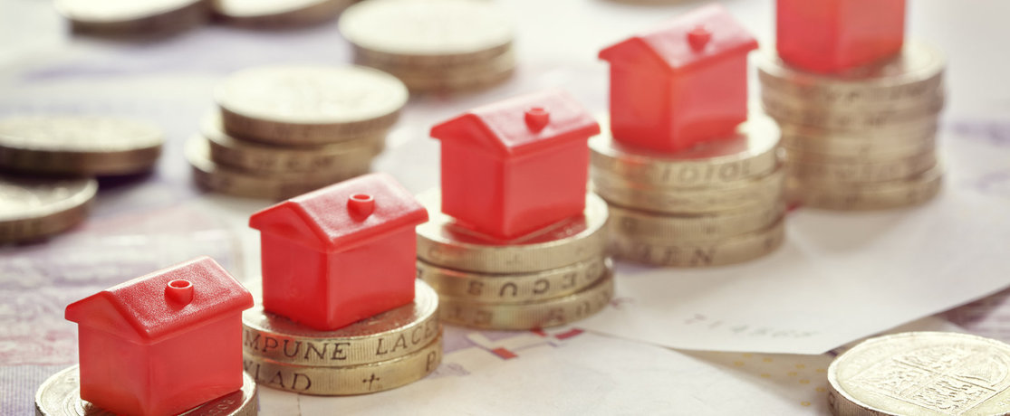 Little red model houses on pound coins rising upwards