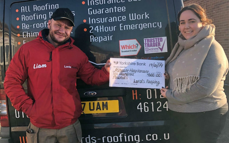 Liam Anderson presenting a charity donation to a local hospice