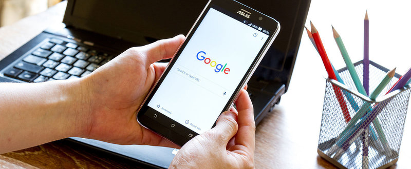 hands holding phone with Google on