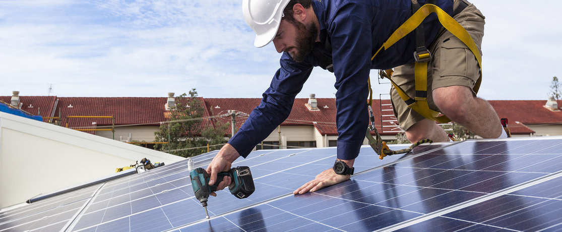 Man wearing a harness installing solar panels on a roof with a drill