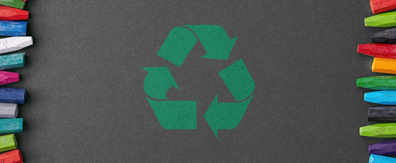 recycling symbol on a board with coloured chalks to the side