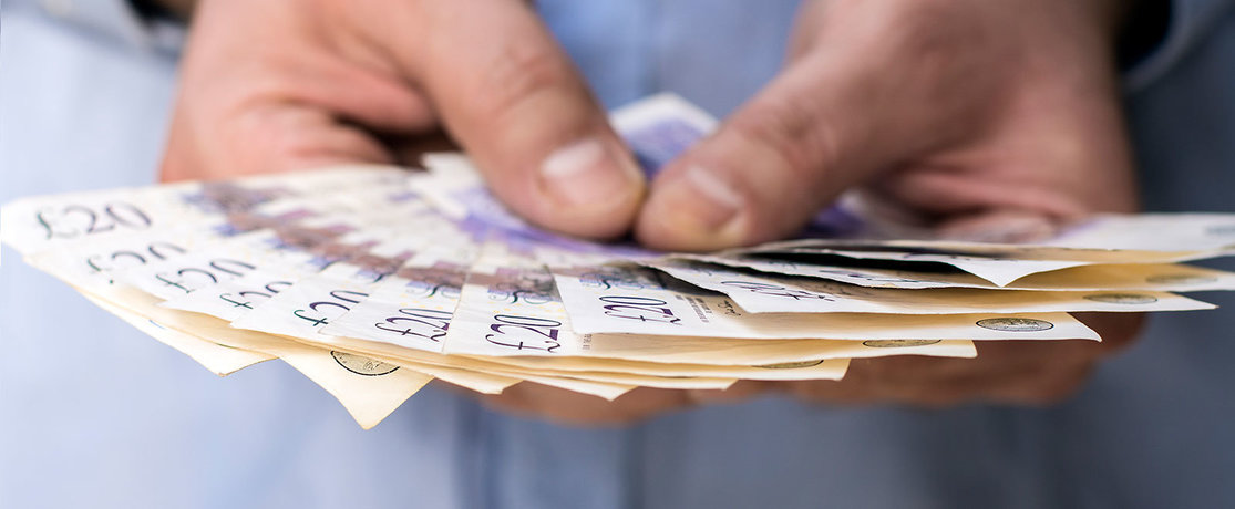 man's hands holding £20 notes in cash
