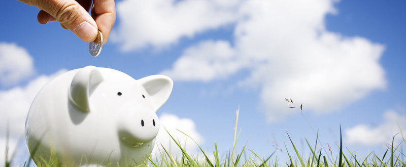 saving for pension in a piggy bank against a blue sky