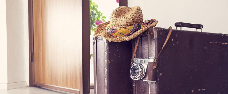suitcases by door, sunhat and camera
