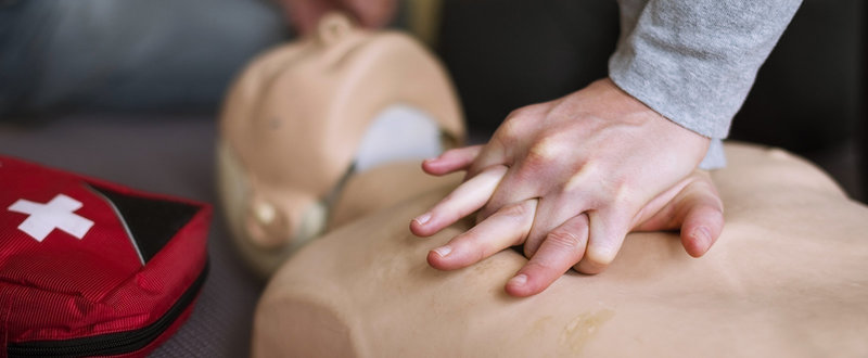 woman's hands practicing CPR in first aid training