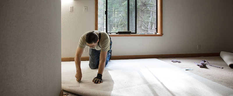 man fitting a carpet
