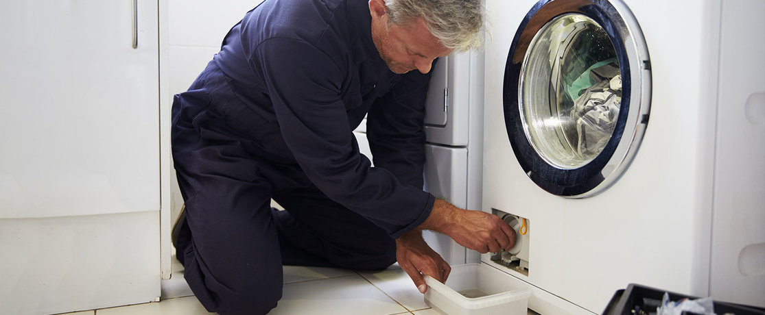 man fixing washing machine