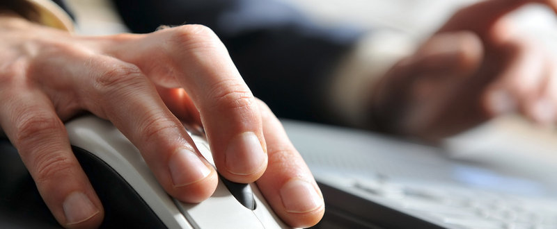 hands clicking mouse by laptop