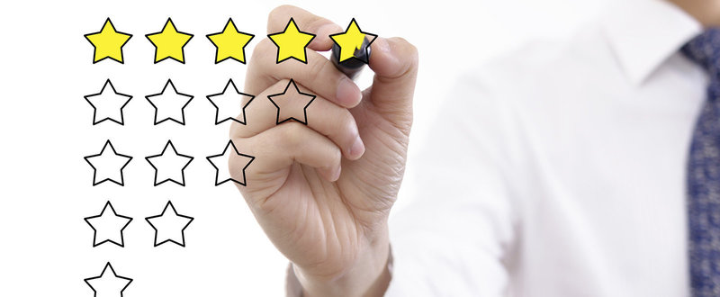 hand filing in a five star review, review template on a screen