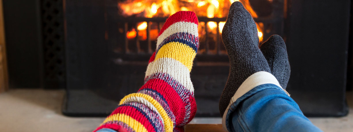 warming feet in socks in front of open fire grate
