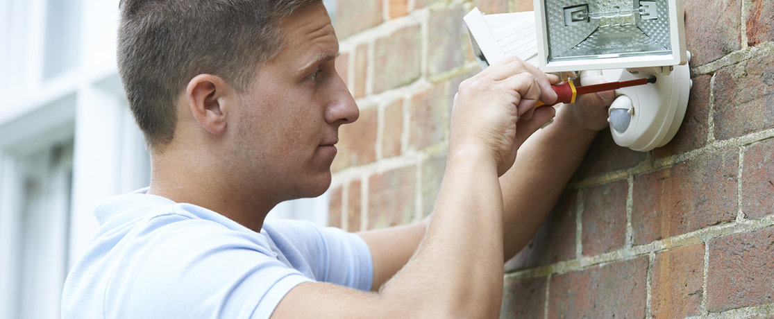 man installing external LED security lighting on an outside wall