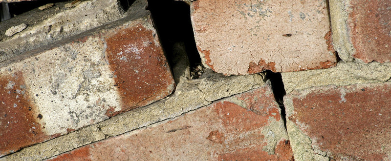 crumbling wall, bricks with broken mortar and hole