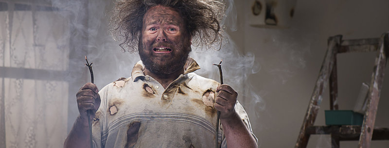 DIY disaster man holding electrical cable with burns on his shirt, plus smoke blackened face