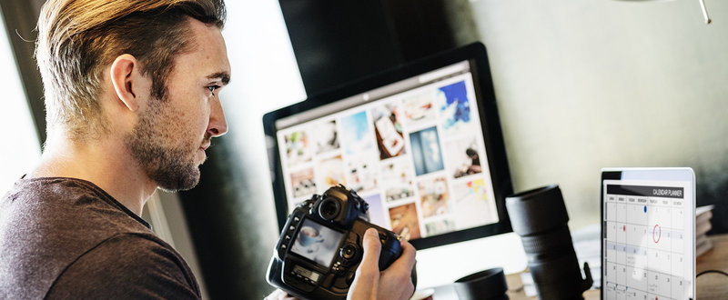 man looking at images on screen from camera