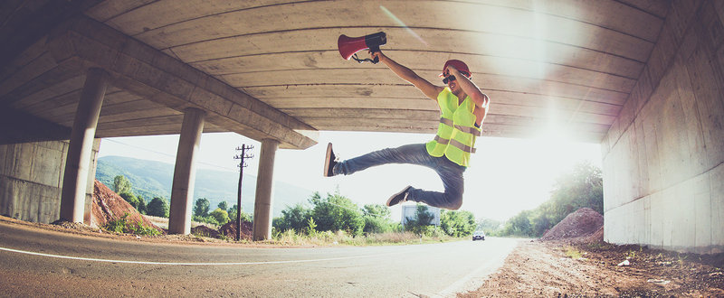 man in a high-viz vest jumping for job under a bridge