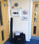 Square thumb fire alarm testing being carried out at a secondary school in hassocks