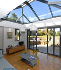 Square thumb orangery with grey aluminium patio doors and an aluminium roof lantern interior sussex