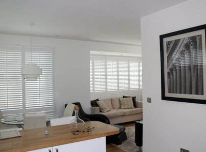 Primary thumb white living room with full length plantation shutters with a mid rail